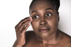 Young African woman touching the skin around her eyes stock photos