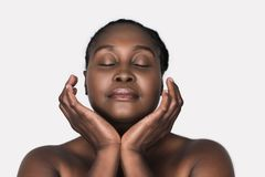 Young African woman with perfect skin against a white background. Young plus size African woman with a perfect complexion standing with her eyes closed and Stock Photos