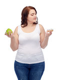 Young plus size woman choosing apple or cookie Stock Photo
