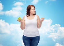 Young plus size woman choosing apple or cookie Stock Images