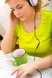 Young plus size woman listening to Audio while working on a lapt Stock Photo