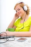 Young plus size woman listening to Audio while working on a lapt Royalty Free Stock Photography