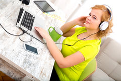 Young plus size woman listening to Audio while working on a lapt Stock Image