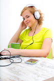 Young plus size woman listening to Audio while working on a lapt Stock Photos