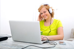 Young plus size woman listening to Audio while working on a lapt Royalty Free Stock Image