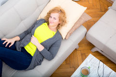 Young plus size woman relaxing on the Sofa Stock Photos