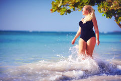 Young plus size woman in swimwear enjoying vacation in water splash on the beach. Young plus size woman in swimwear enjoying vacation in waves on the beach Royalty Free Stock Photos