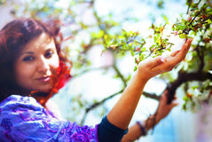Young poetic woman with magnolia tree in the spring time Royalty Free Stock Image