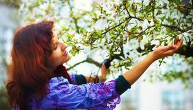 Young poetic woman with magnolia tree in the spring time. Woman holding flower. Royalty Free Stock Photos