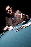 Young poker player. Young man throwing chips on the table while playing poker Royalty Free Stock Image