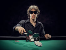 Young poker player throwing chips Royalty Free Stock Images