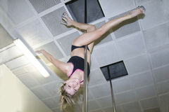 Young pole dance woman upside down in dance hall Royalty Free Stock Image