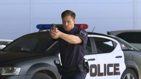 Young police officer aiming gun, detaining criminal outdoors, district security. Stock footage stock footage