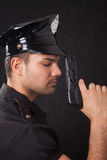 Young policeman looking down. Young handsome policeman with a gun royalty free stock photo