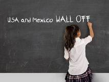 Young political activist schoolgirl writing on school classroom blackboard Mexico and USA wall off. With chalk in no border and land frontier between countries royalty free stock image