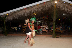 Young Polynesian Pacific Island Tahitian Man Dancer. AITUTAKI - SEP 18:Polynesian Pacific Island Tahitian male dancer in colorful costume dancing with tourist on Royalty Free Stock Photography