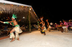 Young Polynesian Pacific Island Tahitian Men Dancers. Polynesian Pacific Island Tahitian male dancers in colorful costume dancing on tropical beach Stock Image