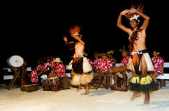Young Polynesian Pacific Island Tahitian Men Dancers. Polynesian Pacific Island Tahitian male dancers in colorful costume dancing on tropical beach Royalty Free Stock Photos