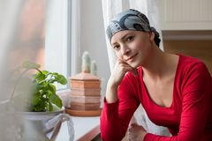 Young positive adult female cancer patient sitting in the kitchen by a window, smiling. Young positive adult female cancer patient sitting in the kitchen by a Royalty Free Stock Images