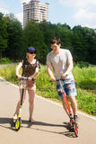 Young positive athletic couple riding scooter in city park Stock Image