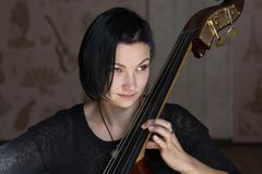 Young positive brunette playing double bass. Portrait royalty free stock photos
