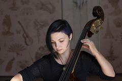 Young positive brunette playing double bass. Portrait stock photography
