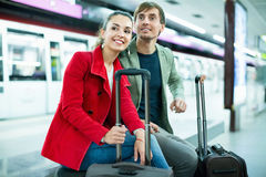 Young positive cheerful passengers with luggage waiting for train royalty free stock photo