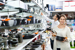 Young positive couple in the cookware section Royalty Free Stock Images