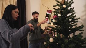 Young positive couple decorating the Christmas tree in the room before holiday. New Year and Christmas time concept. Young positive couple decorating the stock video footage