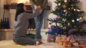 Young positive couple decorating the Christmas tree together in the room before holiday. New Year and Christmas time. Concept stock video footage