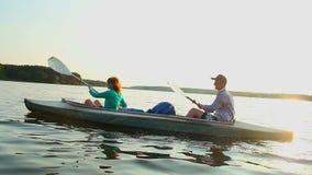 Young positive couple paddling kayak at sunset, beautiful view. Stock footage stock video