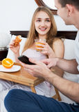 Young positive couple reading news from smartphone Royalty Free Stock Images