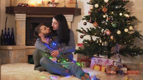 Young positive couple sitting at the Christmas tree on the floor in the room. New Year and Christmas time concept. Happy. Family celebrating holidays stock video footage