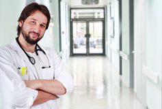 Young positive doctor. On his workplace Stock Images