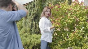 Young positive girl in white shirt and jeans posing near the berry bush for the young man with camera outdoors. Male. Photographer taking photos of attractive stock video