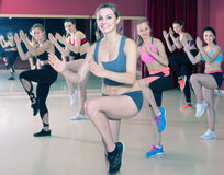 Young positive girls performing modern dance in fitness studio stock photo