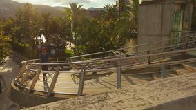 Young positive guy with backpack walking up the stairs in beautiful resort town. Stock footage stock video