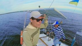 Young positive guy and senior man on deck fast-sailing yacht. Stock footage stock video footage