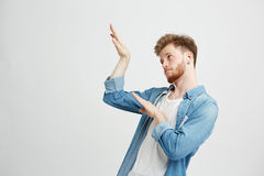 Young positive handsome man in headphones listening to music dancing moving over white background. Copy space Royalty Free Stock Photos