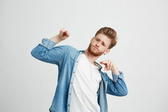 Young positive handsome man in headphones listening to music dancing moving over white background. Copy space Royalty Free Stock Image