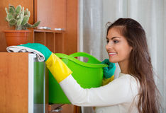 Young positive  long-haired woman doing regular clean-up Stock Photos