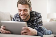 Young man with tablet computer in their hands, on the couch at home. Young positive man with tablet computer in their hands, on the couch at home Royalty Free Stock Image