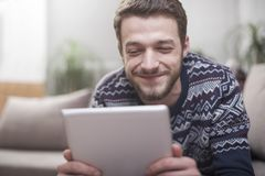 Young man with tablet computer in their hands, on the couch at home. Young positive man with tablet computer in their hands, on the couch at home Stock Photography