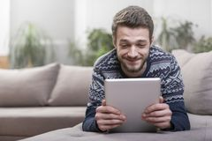Young man with tablet computer in their hands, on the couch at home. Young positive man with tablet computer in their hands, on the couch at home Royalty Free Stock Photos