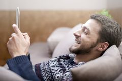 Young man with tablet computer in their hands, on the couch at home. Young positive man with tablet computer in their hands, on the couch at home Stock Images