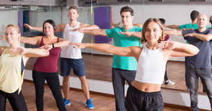 Young positive  people studying zumba elements. In dancing hall Royalty Free Stock Photos