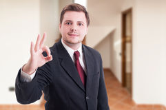 Young positive realtor showing ok sign Stock Photo