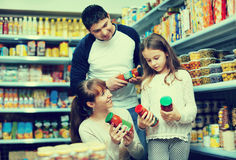 Young positive smiling parents with little girl buying tinned Stock Photos