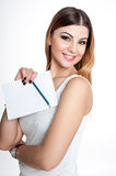 Young positive smiling student girl with notebook and pen planning her daily schedule wearing casual white t-shirt on white. Studi Stock Photo