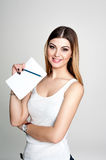 Young positive smiling student girl with notebook and pen planning her daily schedule wearing casual white t-shirt on white. Studi Royalty Free Stock Image